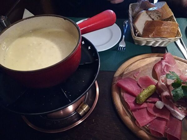 テーブル左手のフォンデュ鍋にとろけたチーズが入っている。右上にはパンの入ったかご、右下にはハムやピクルスののった皿がある。