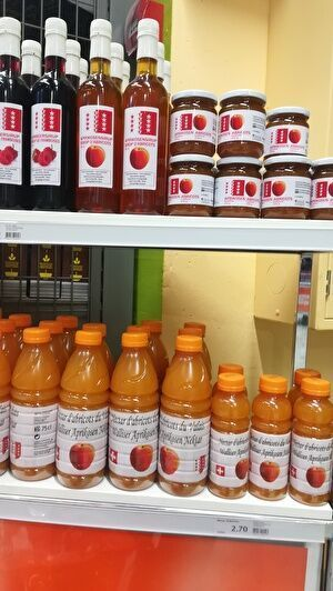 スーパーの棚に並ぶアプリコットの加工品。シロップ、ジャム、ジュースが並ぶ。