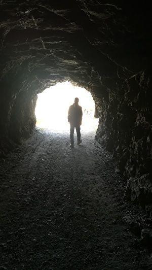 トンネルの向こうに外に光が見える。光の中に男性が立っている影が見える。