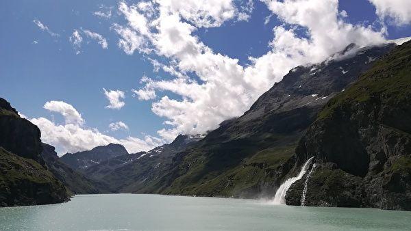 ダムの湖に山から水が流れ込んでいる。青空と白い雲を背景に山と湖が映えている。