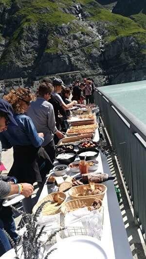 バイキングテーブルの前に並び食べ物を皿にとる人々。