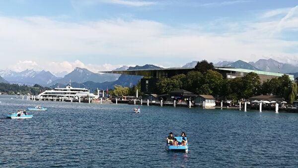 ルツェルンの湖の景色。ボートを楽しむ人々や遊覧船。遠景には雪をかぶったスイスの山なみ。