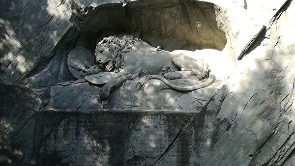 崖に彫り込まれたひん死のライオン像。木の影が映っている。