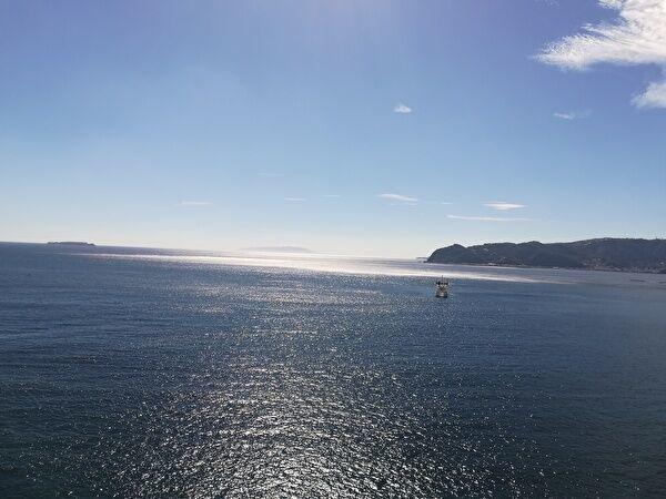 青空の下に輝く海。一隻の船が見える。