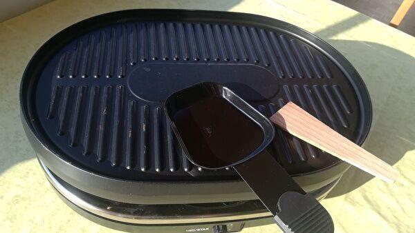 家庭用ラクレット調理器。鉄板の上に小さな金属製の皿と木のへらがのっている。
