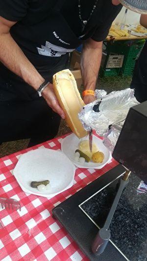 とろけたチーズをナイフで皿にけずり落としている。