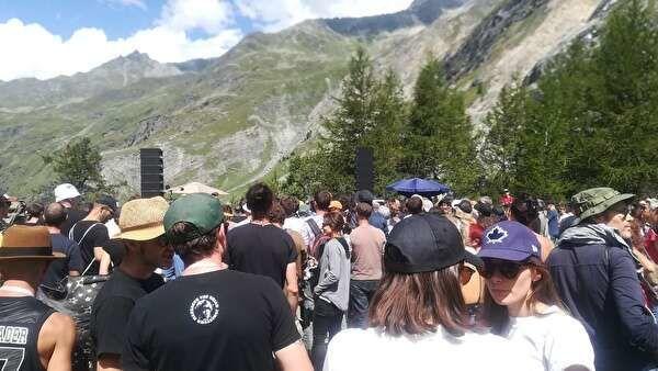 ロックの野外コンサートを楽しむ人々。遠景に山が見える。