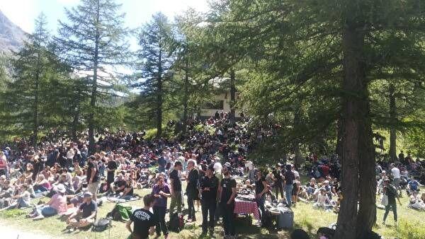 木々の間に座ってコンサートを楽しむ人々。