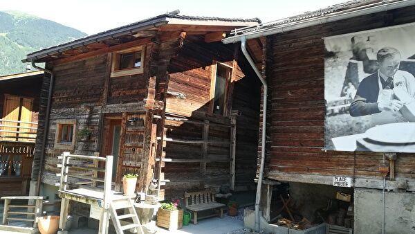 伝統的なスイスのシャレーが並んでいる。木の壁にラクレットを調理する人の白黒の写真が飾られている。