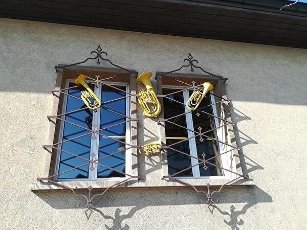 白いぬりかべの家の窓。おしゃれなデザインの鉄格子にトランペットの飾りがついている。