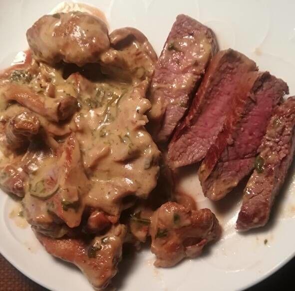 切り分けられたラム肉のステーキ。中身がほんのりピンク色にきのこクリームが添えられている。