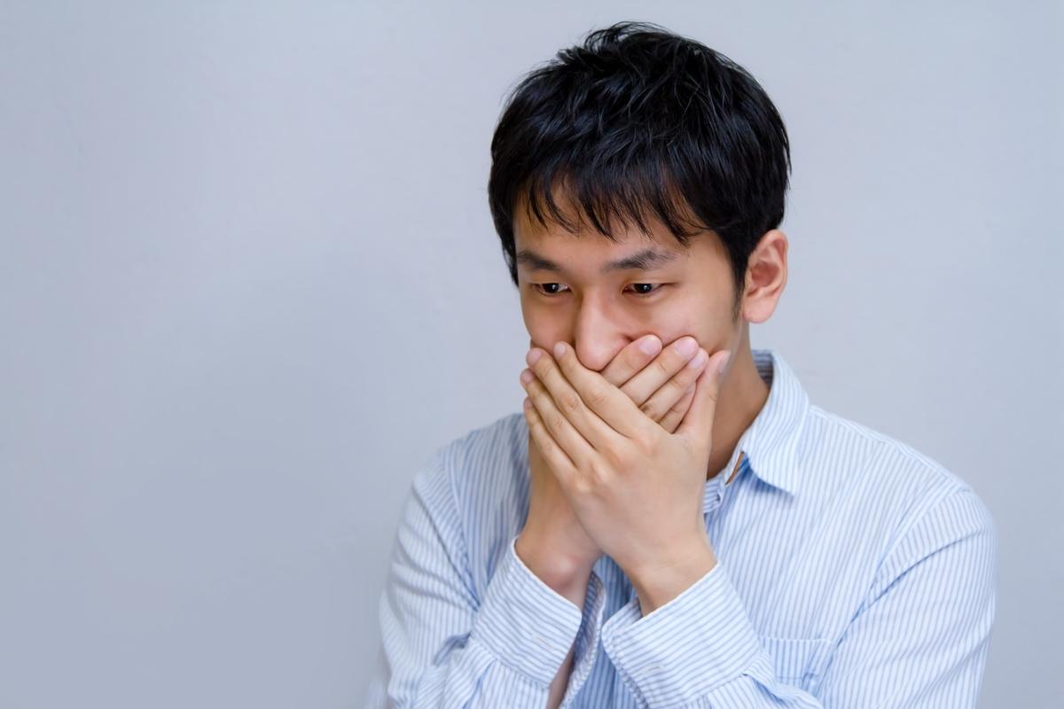 口を手で覆う男性