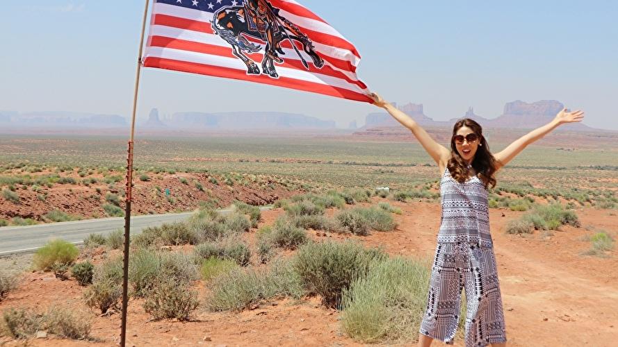広大な背景をバックに映るアメリカの国旗と女性
