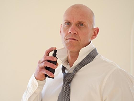 香水をつけて匂いケアするアメリカ人男性
