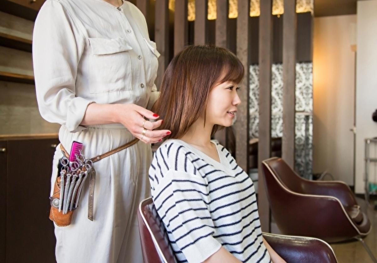 アメリカの美容室で髪を切る前に相談している女性(イメージ)