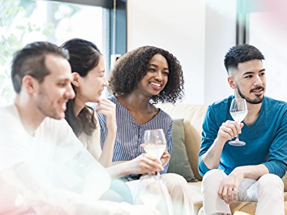 グラスを持っておしゃべりするアメリカのパーティ男女(イメージ)