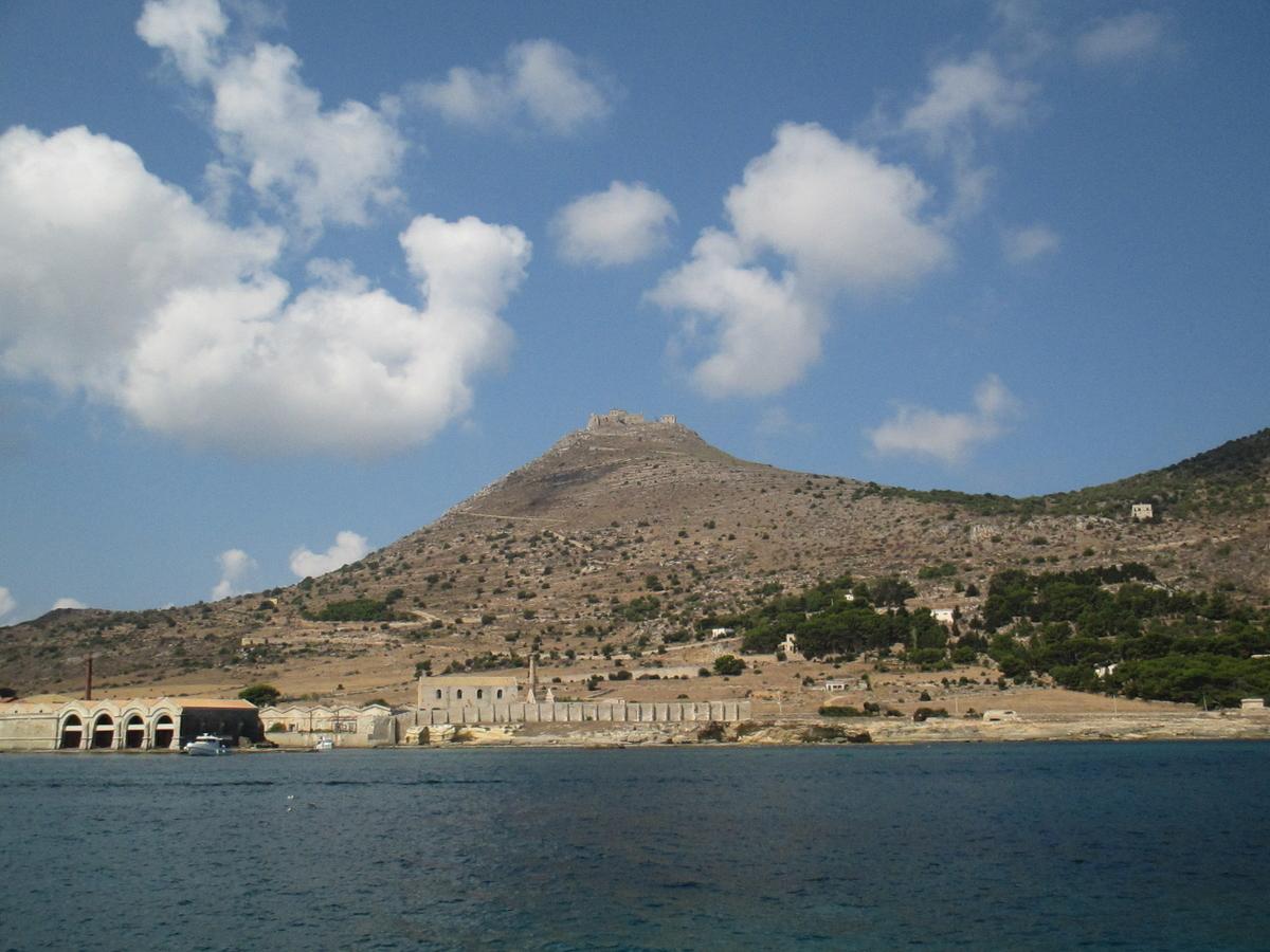 海からファビニャーナ島とその山を臨む