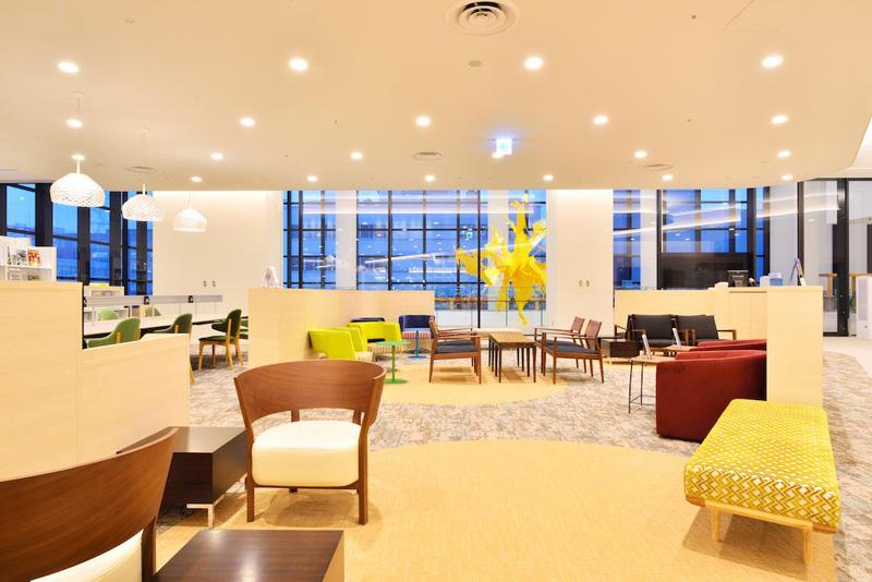 札幌市図書・情報館 さまざまなデザインの椅子 ガラスのむこうに黄色いオブジェ
