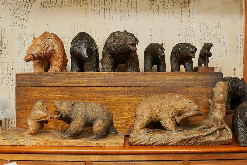 木彫り熊や熊形グッズが並ぶ山里稔さんのアトリエ