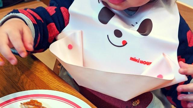 子供用エプロンを着けてご飯を食べる子供の写真