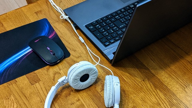 机の上のパソコン、ヘッドカム、マウスの写真