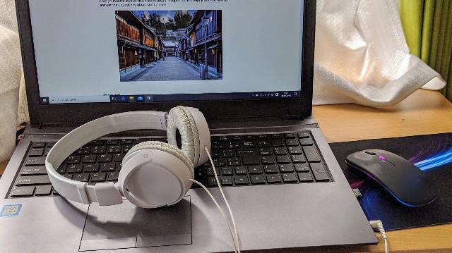 オンライン英会話のページを開いたパソコンとヘッドホンとマウスの写真