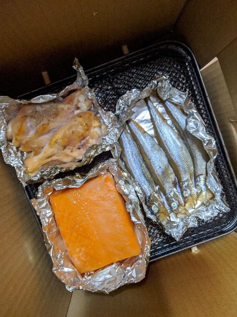 自宅のベランダで燻製した食材の写真(サーモン、シシャモ、肉)