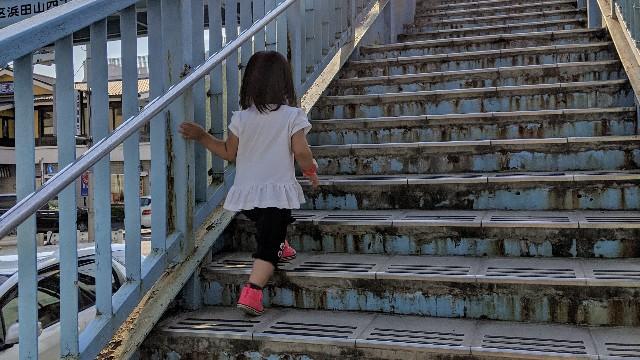 歩道橋を上る2歳の子どもの写真