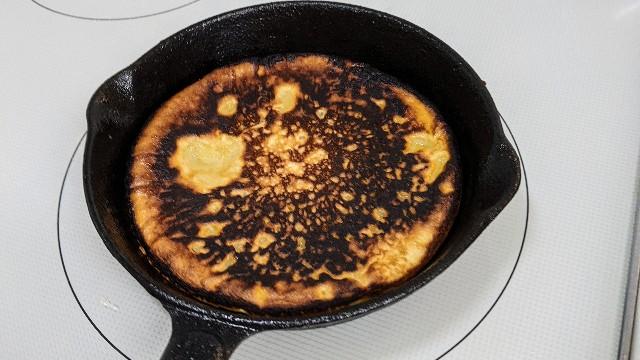 スキレットでちょっと焦げたパンケーキを焼いている写真