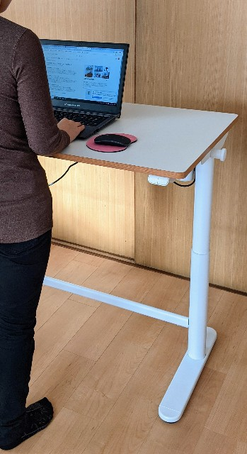 FlexiSpotの昇降式学習机の最高高さに大人(女性)が立った写真