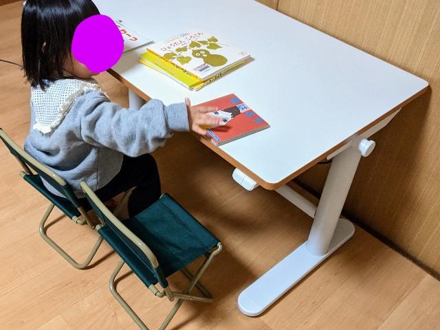 FlexiSpotの昇降式学習机で子供が絵本を読んでいる写真