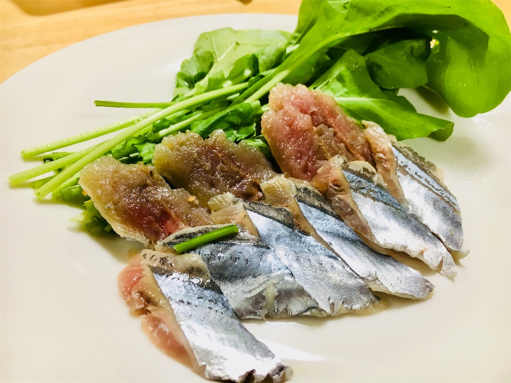 秋刀魚とルッコラを皿に並べる