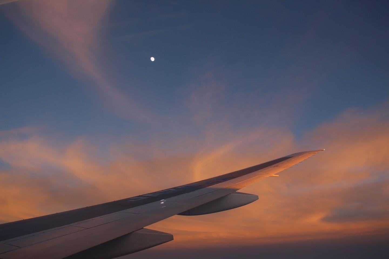 飛行機から夕焼けと月の写真