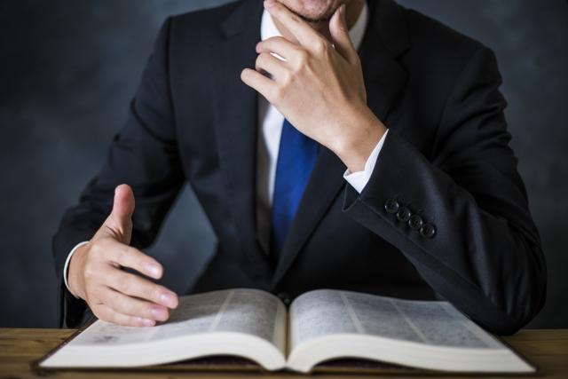 本を開くスーツ姿の男性の写真