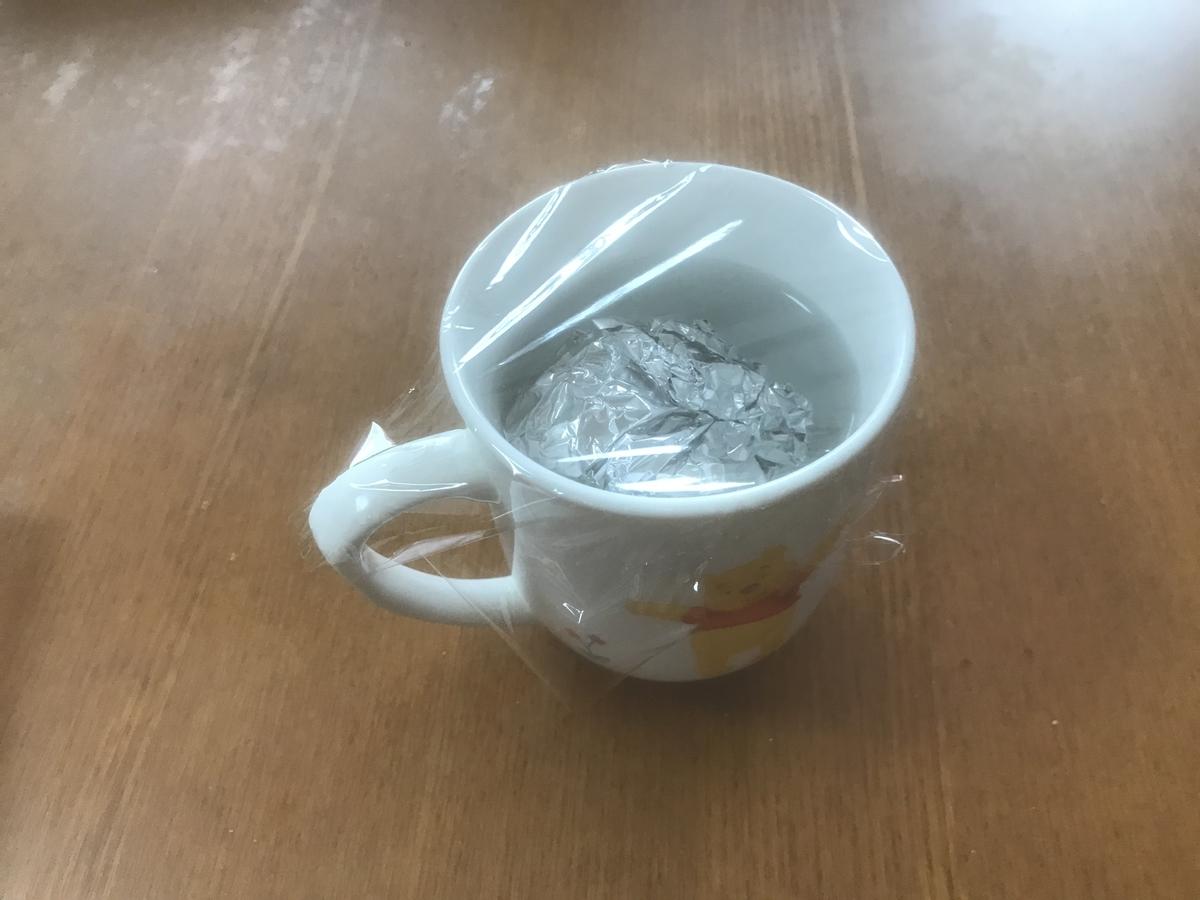 水を注いだ耐熱マグカップにラップを張る