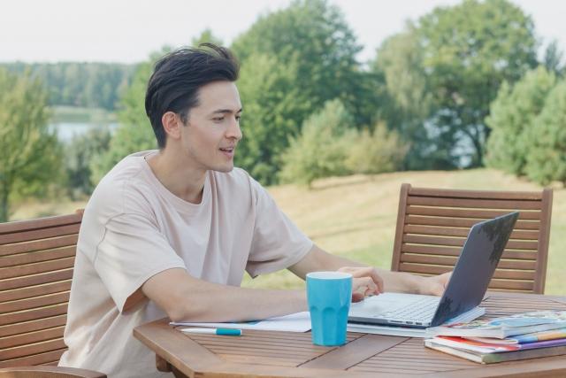 自然の中でパソコンを使う男性