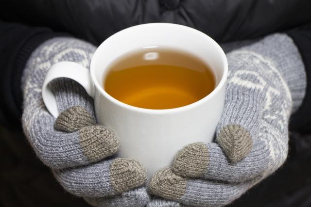手袋をはめて持つ熱いお茶が入ったカップ