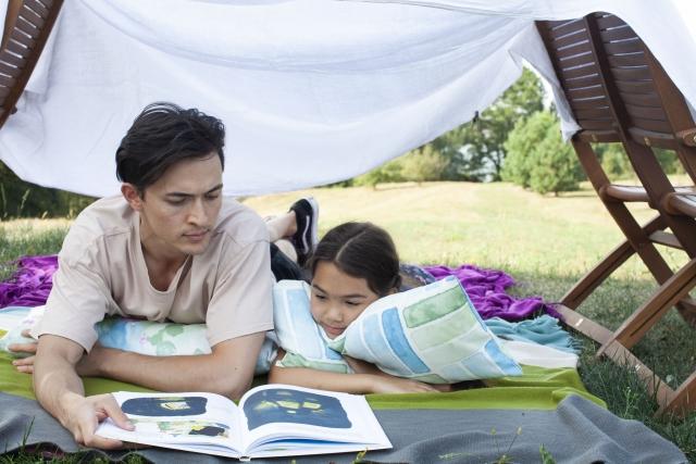 寝転んで本を読む親子