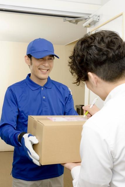 荷物の受取のサインをする男性