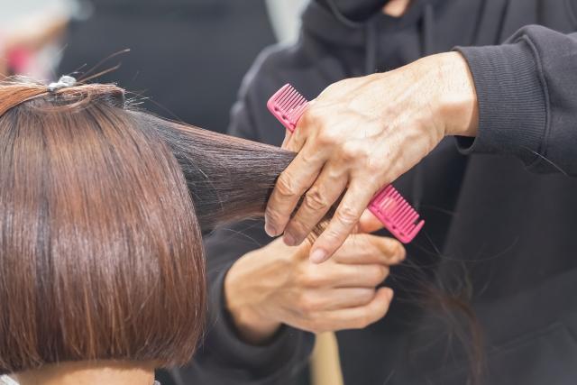 ヘアサロンで髪の毛をカットする美容師の手元