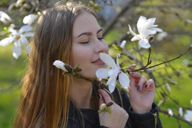 花の香りを嗅ぐ女性