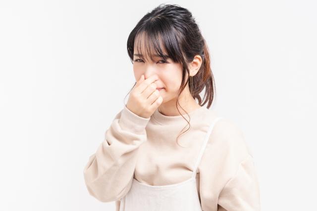鼻をつまむ若い女性