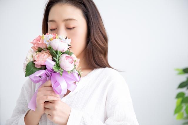バラの香りを嗅ぐ女性