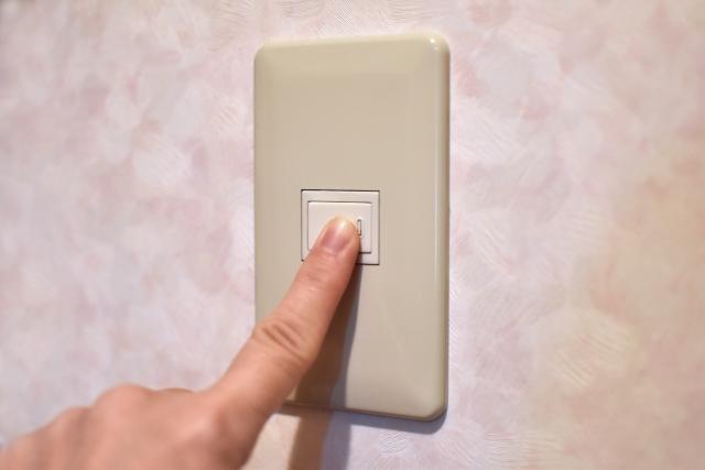 電気のスイッチを切って節電する人