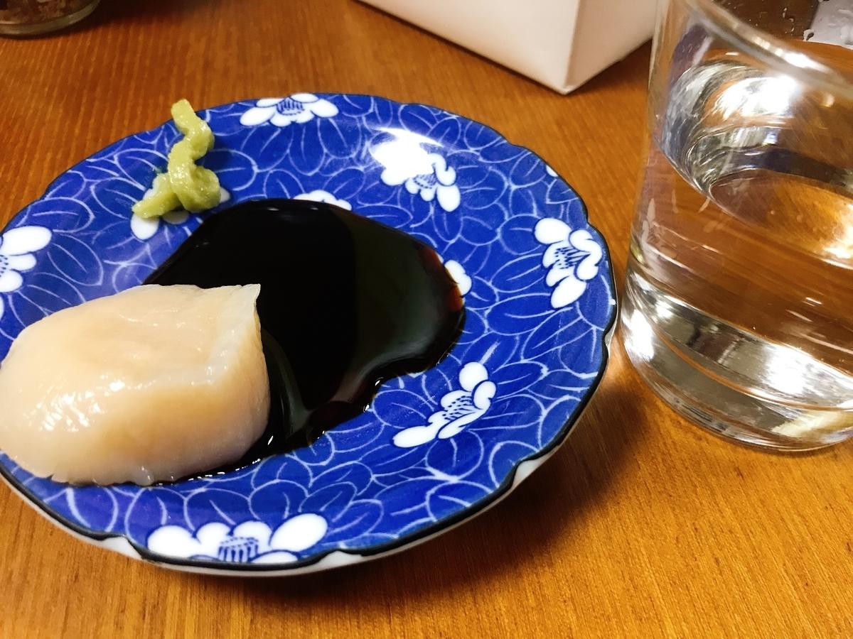 北海道から直送されたホタテ貝の貝柱の刺身に稲竹商店のカネマサ醬油の刺身醤油をつけた画像