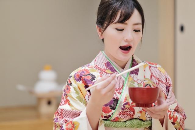お雑煮を食べる着物姿の女性