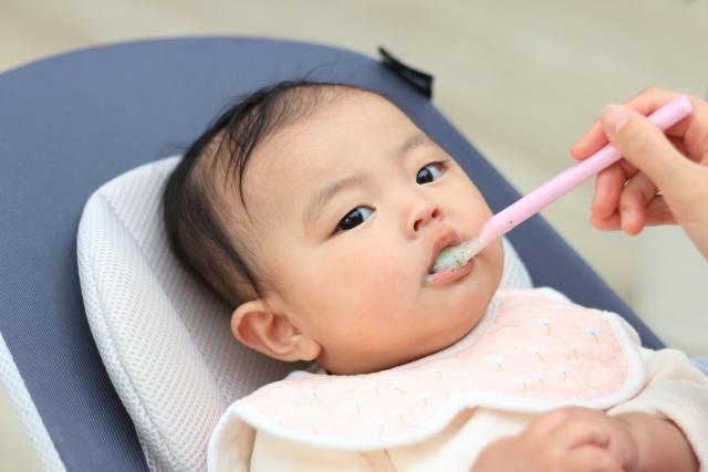離乳食を食べさせてもらっている赤ちゃん