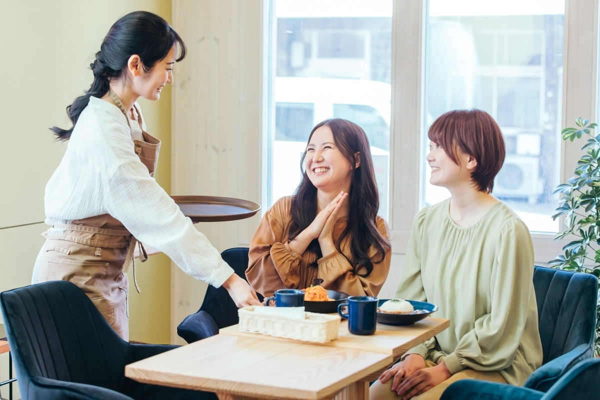 女子会でコーヒーを飲みながら楽しそうな会話をしている様子