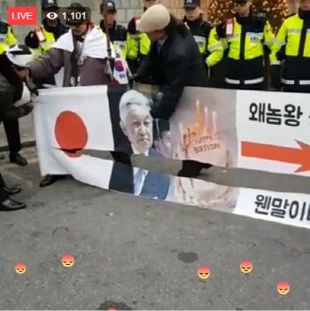 日本国旗と上皇の写真入り横断幕を切り刻むデモ隊