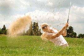 ラフからスライスショットを打つ女性ゴルファー